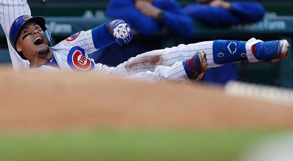 Chicago Cubs' Javier Baez reacts after hitting an
