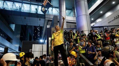 A protester waves a Hong Kong flag outside