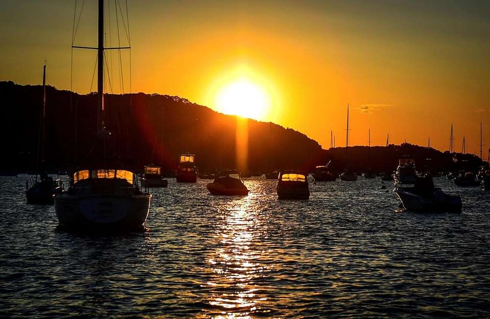 The Sun sets behind boats moored in Northport