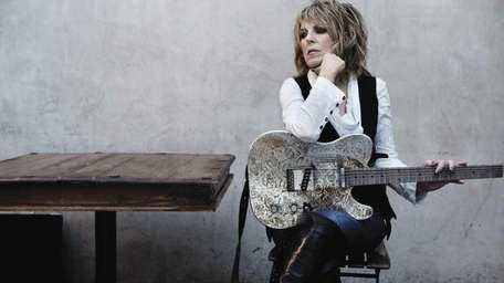 Lucinda Williams sits with her guitar for a