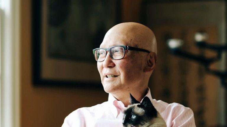 Dr. Ron Naito cuddles his cat, Dolly, at