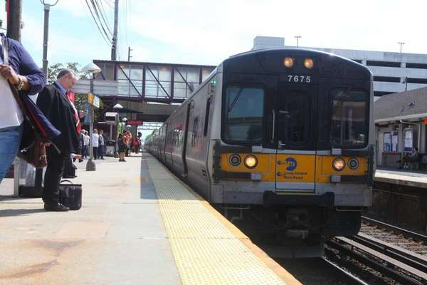 An LIRR train pulling into the Mineola station.