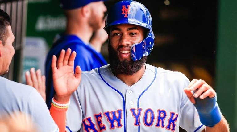 Mets shortstop Amed Rosario celebrates after scoring on