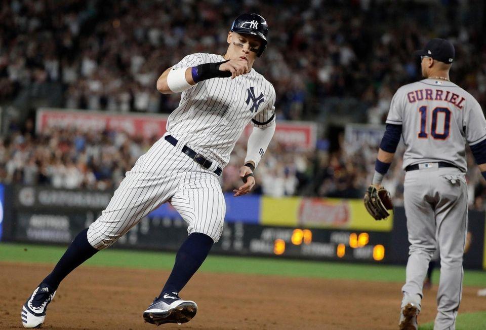 New York Yankees' Aaron Judge, left, runs past