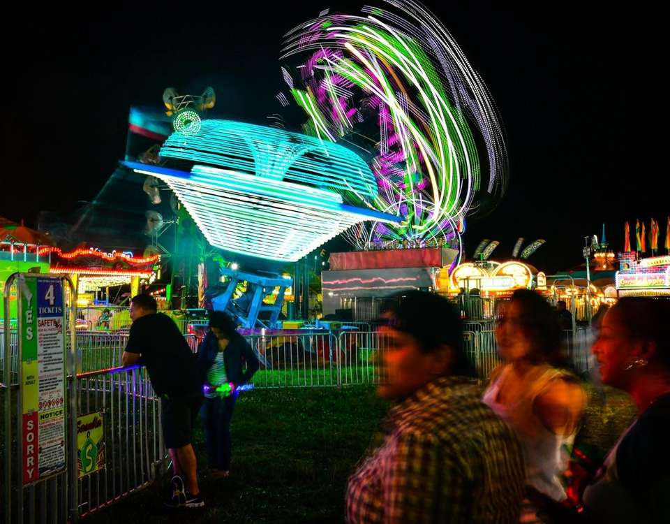 Amusement park rides spin as people attend the