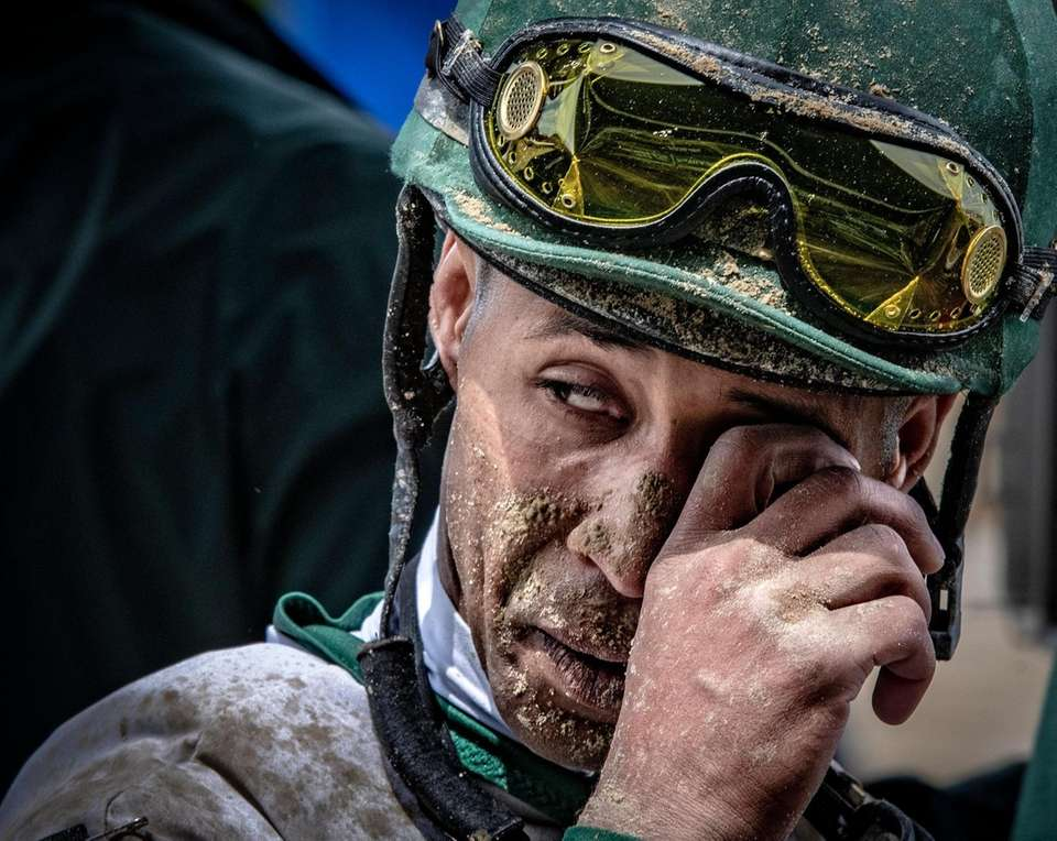 A jockey is covered in mud after his