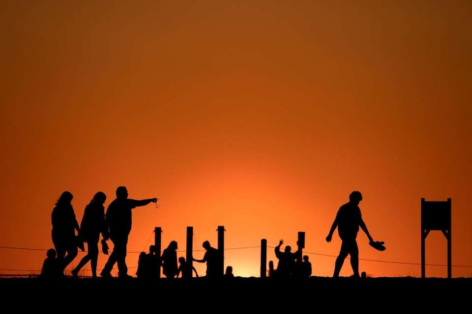 Beachgoers retreat as the sun sets at Robert