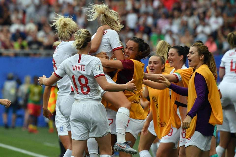England's defender Alex Greenwood (C) is congratulated by