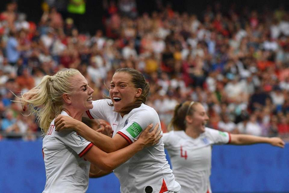 England's defender Alex Greenwood (L) is congratulated by
