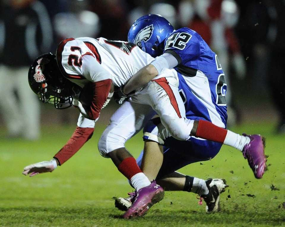 Hauppauge's Ryan Henry, right, tackles Half Hollow Hills