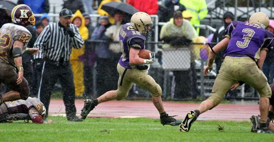 Sayville's running back goes around the end, and