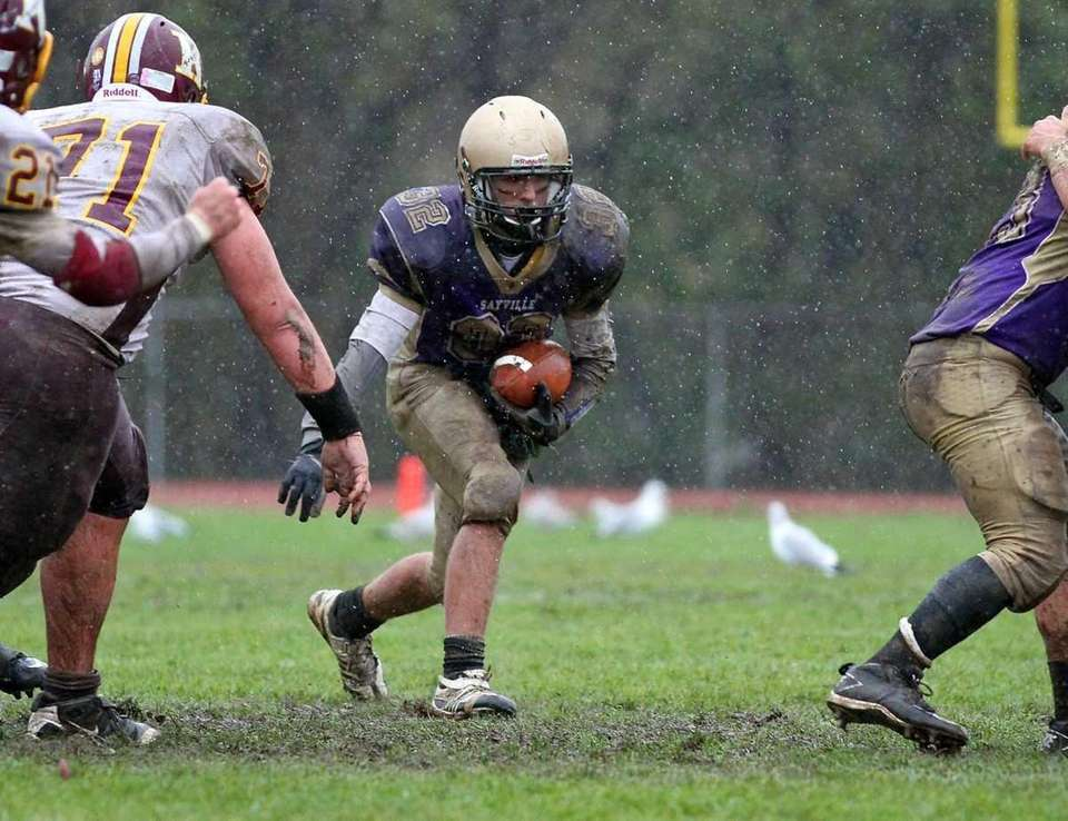 Sayville's quarterback tries to get his footing through