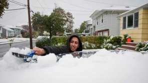 Michael Neiss uncovers his car with snow in