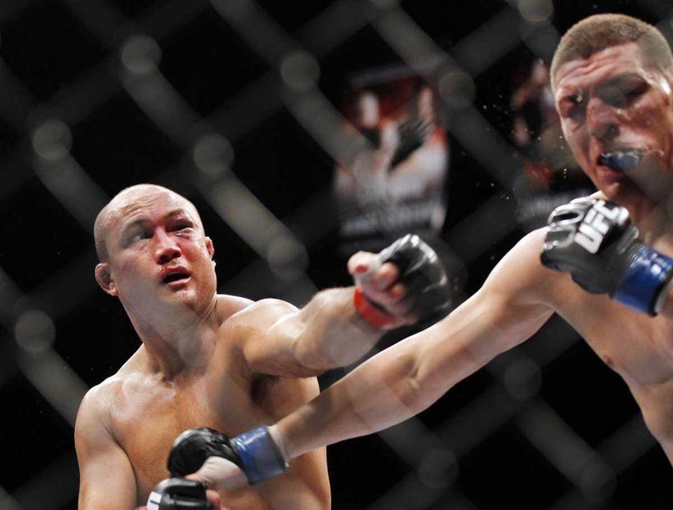 BJ Penn, left, punches Nick Diaz during their