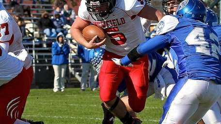Newfield's Ron Denig powers his way past the