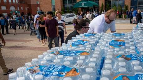 Residents line up to receive water on Friday