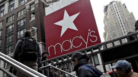 Pedestrians walk outside Macy's, which announced it will