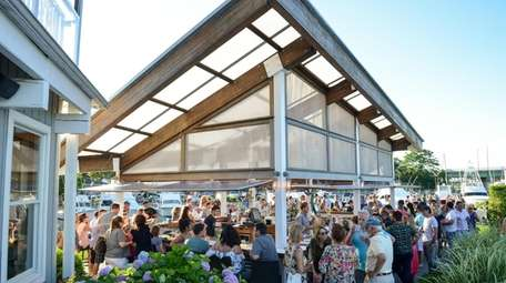 Patrons linger at the outdoor bar to nibble