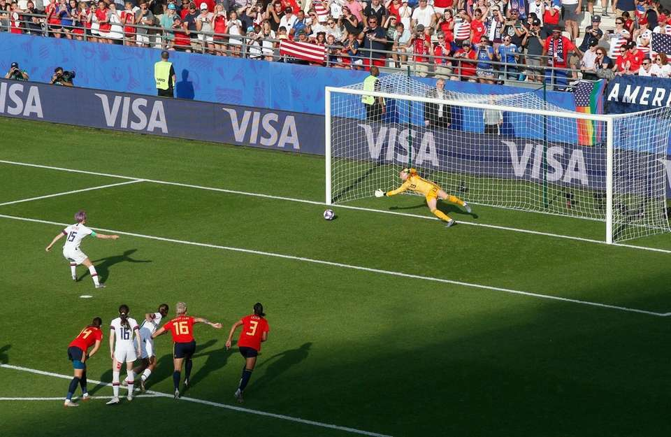 United States' Megan Rapinoe, left, scores her side's
