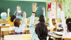 Children raising hands in classroom.