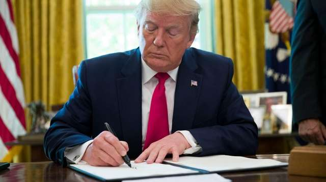 President Donald Trump signs an executive order to