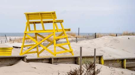 A lifeguard's chair sits away from the water's