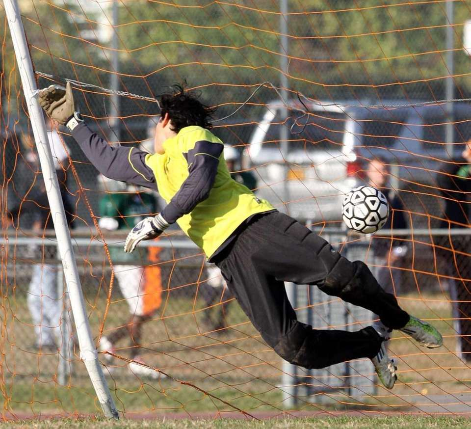 Elmont's goalie Alejandro Servin watches penalty kick get