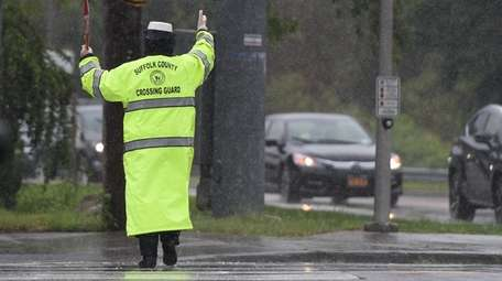 A crossing guard directs traffic on Route 25A