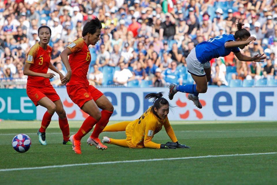 Italy's Elisa Bartoli, right, jumps over China goalkeeper