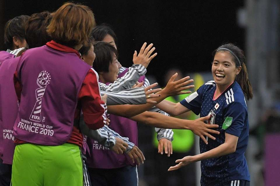 Japan's midfielder Yui Hasegawa (R) is congratulated by