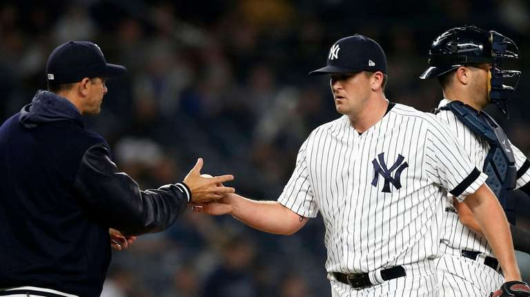 Jonathan Holder #56 of the Yankees hands the