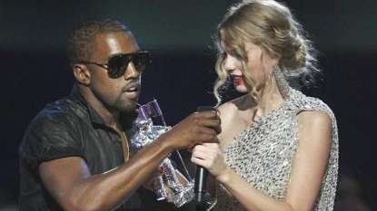 Singer Kanye West takes the microphone from singer