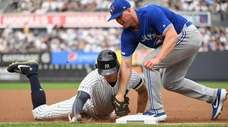 Yankees leftfielder Giancarlo Stanton is tagged out at