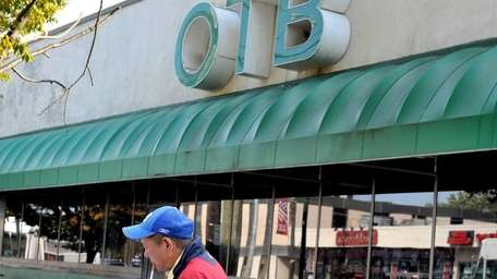 An unidentified man reads a betting sheet in