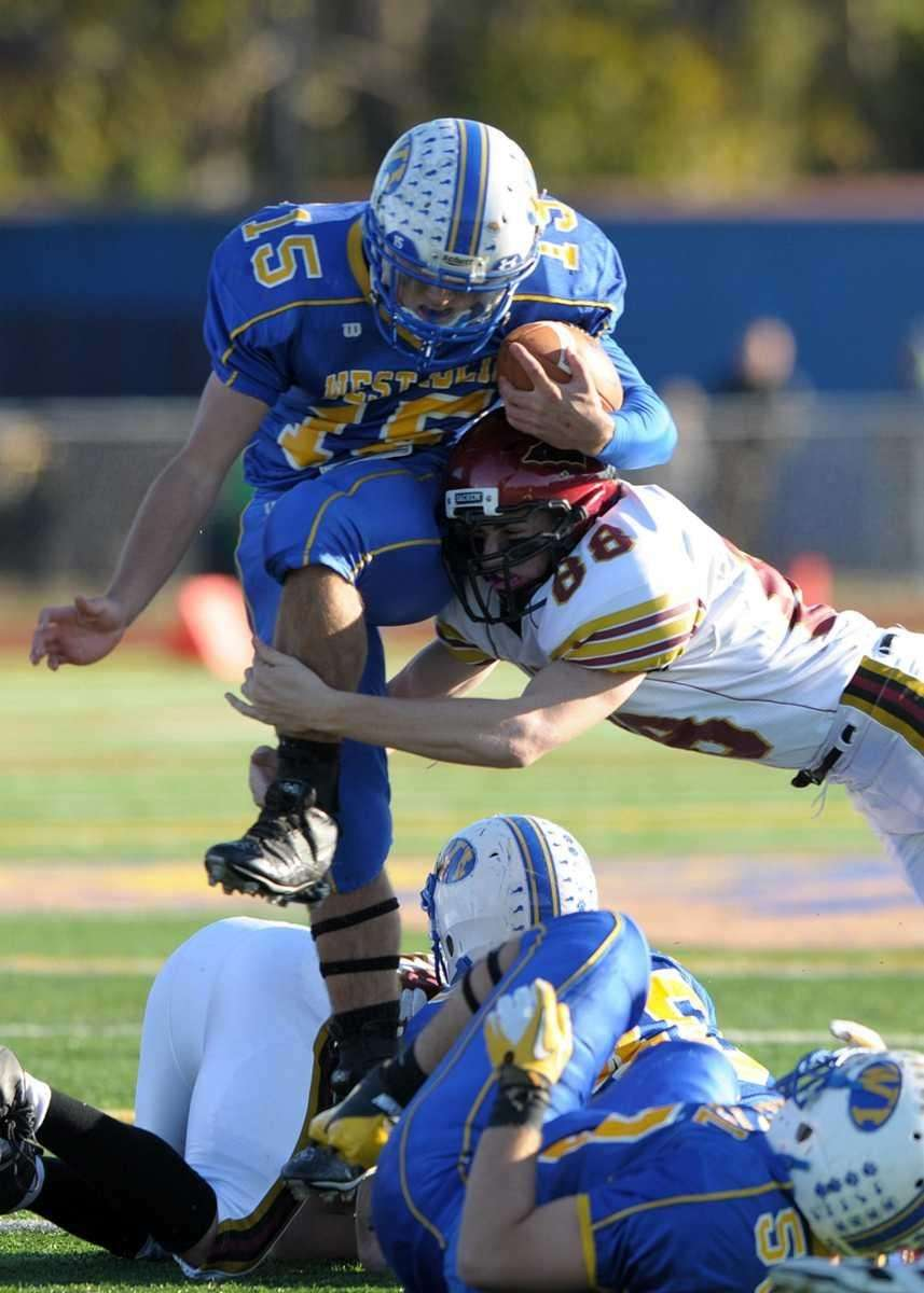 West Islip's Anthony Santo (15) is hit by
