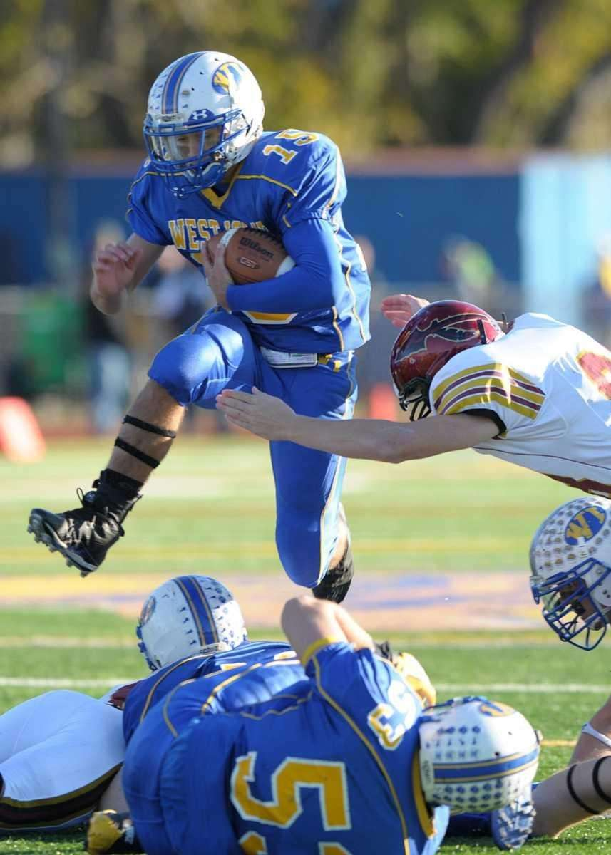 West Islip's Anthony Santo (15) hurdles over the