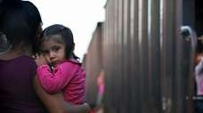 A migrant mother and child wait for a