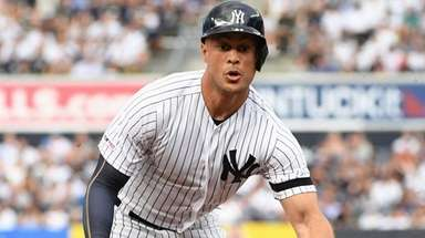 The Yankees' Giancarlo Stanton dives to third base