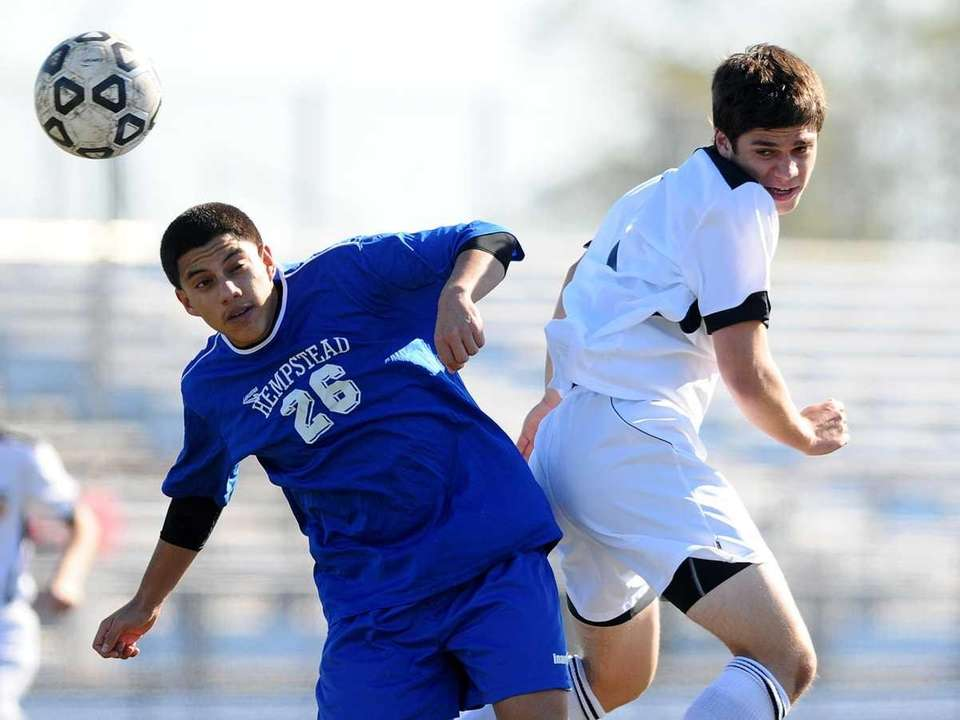 Great Neck South's William Rezin, right, heads a
