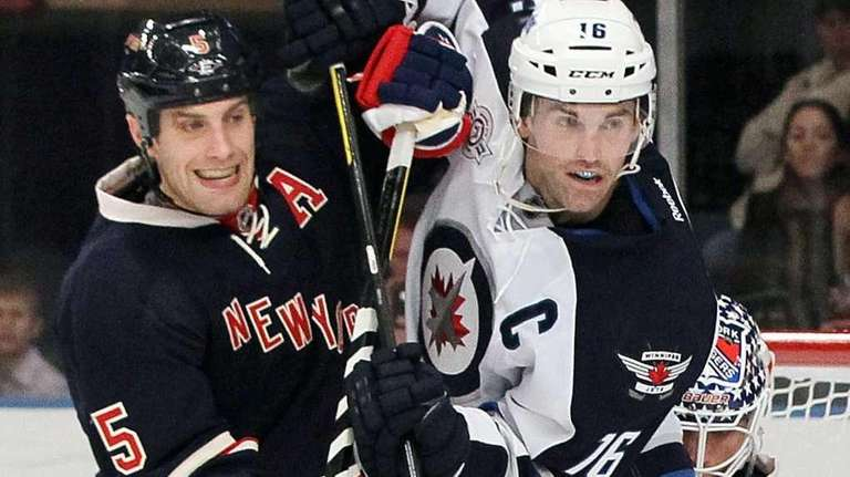 The Jets' Andrew Ladd battles for position against