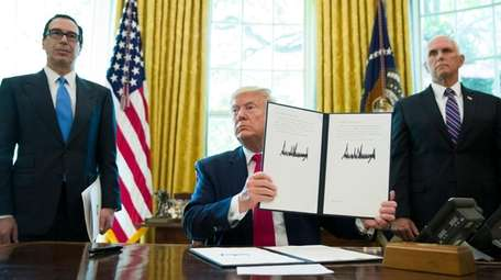 President Donald Trump holds up a signed executive