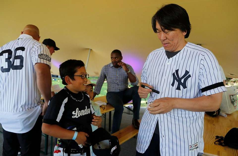 Former Yankee Masahiro Tanaka signs a ball for
