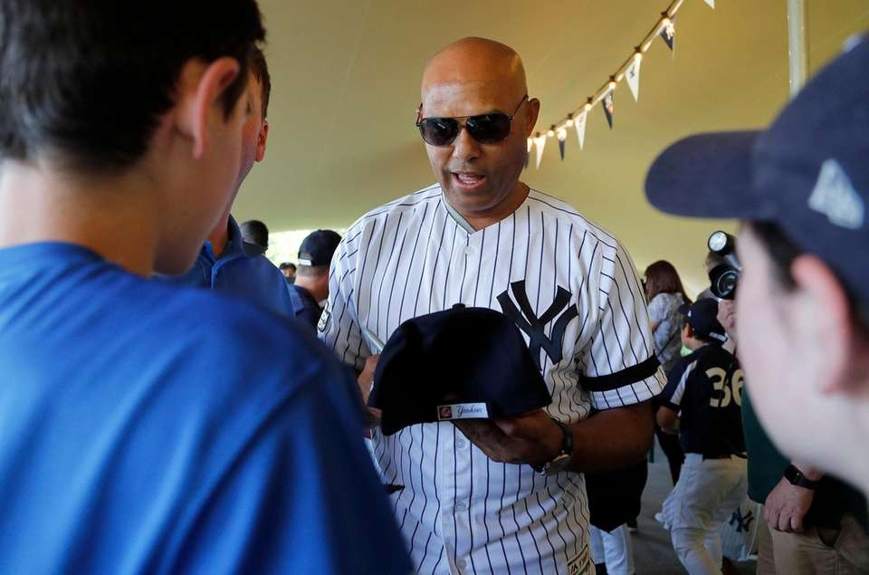 Former Yankee Mariano Rivera signs baseball cap for