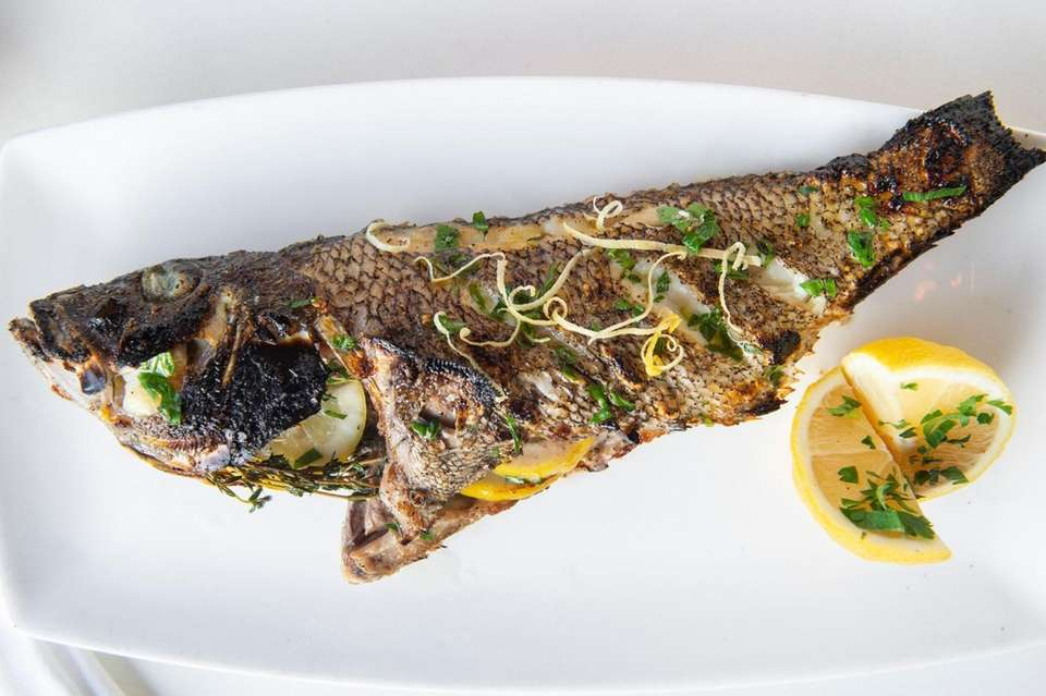 Whole, oven-roasted black sea bass with caponata, as