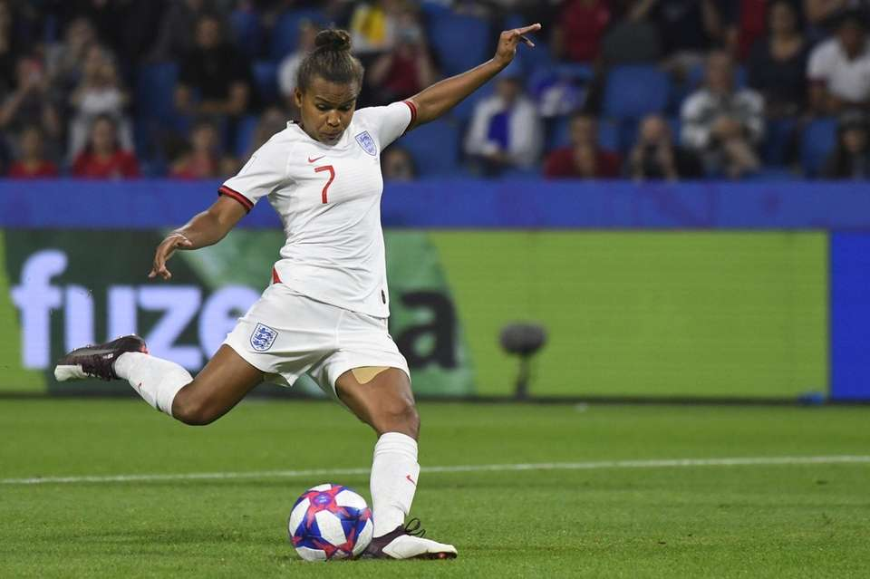 England's forward Nikita Parris kicks and misses a