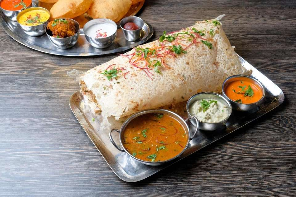 A large pillowy dosa served with several chutneys