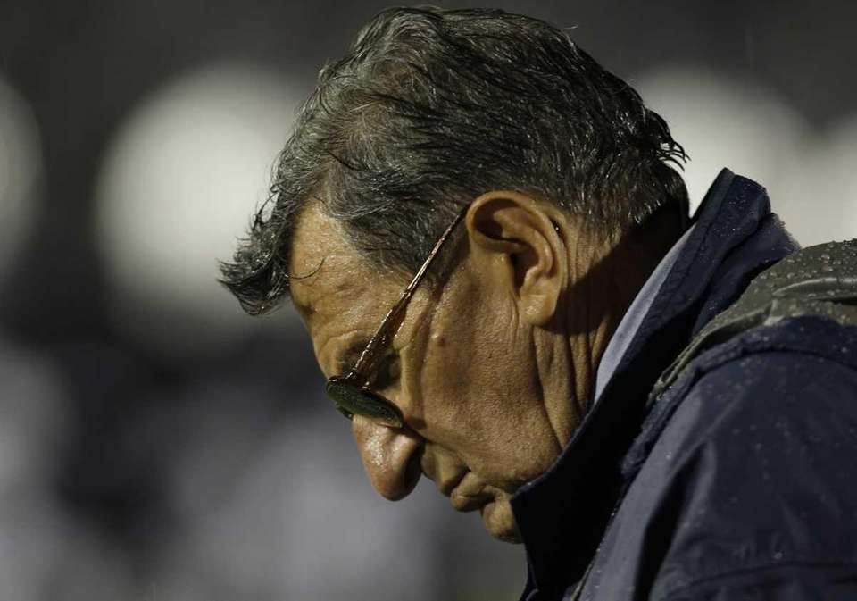 Penn State football coach Joe Paterno stands in