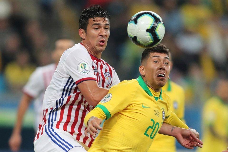 Paraguay's Fabian Balbuena, left, and Brazil's Roberto Firmino