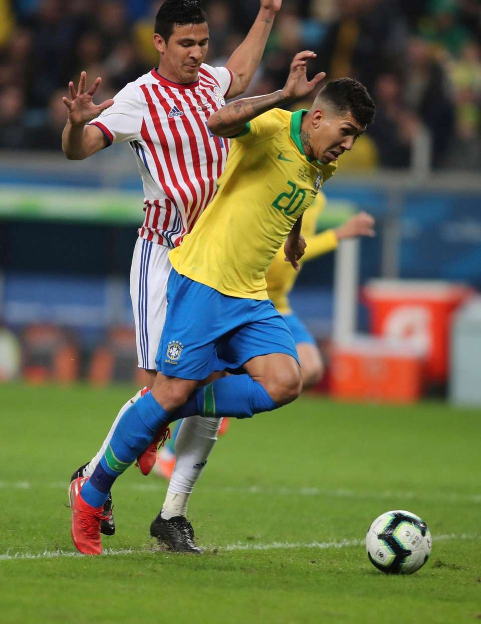 Brazil's Roberto Firmino, front, is tackled by Paraguay's
