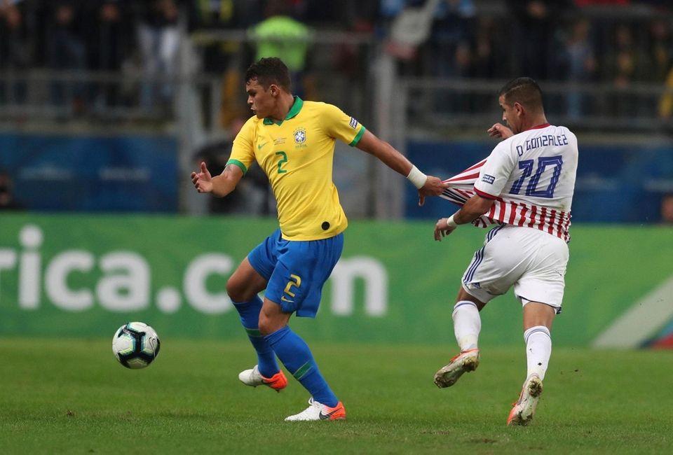Brazil's Thiago Silva, left, and Paraguay's Derlis Gonzalez
